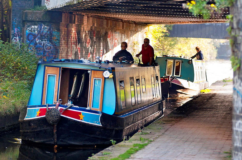 Boats go under a railway bridge on the Birmingham & Worcester canal at Selly Oak, Birmingham, UK