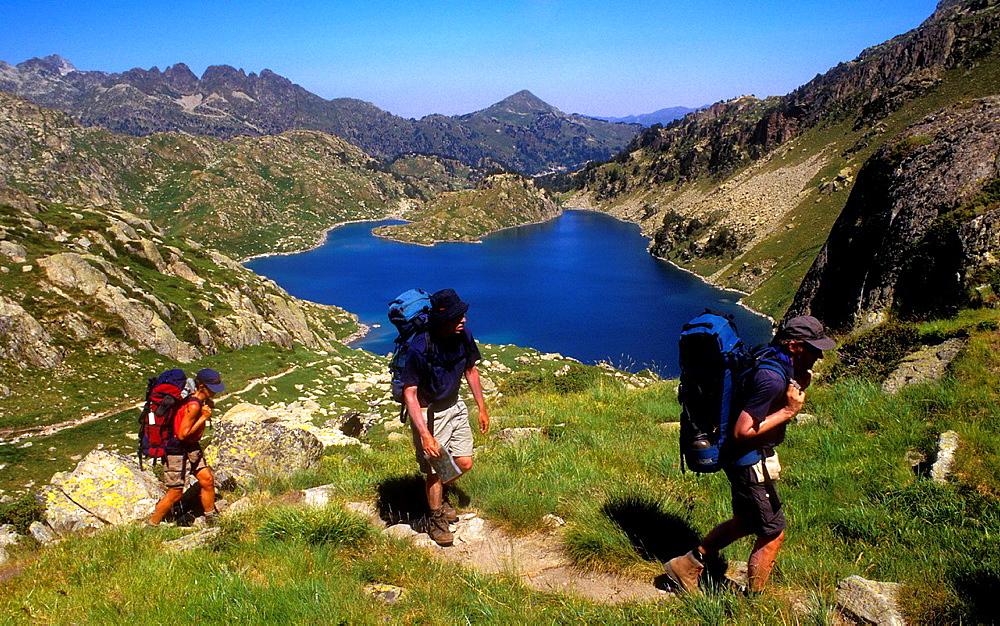 Hikers in 'Estany Obago', Obago lake, Colomers cirque, Aran Valley, Aiguestortes and Estany de Sant Maurici National Park, Pyrenees, Lleida province, Catalonia, Spain