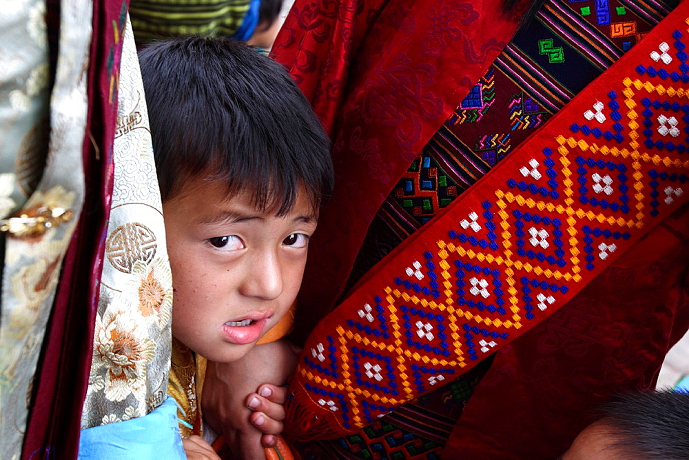 Child appearing from two women at the Thimphu festival tsechu, Bhutan - 817-369347