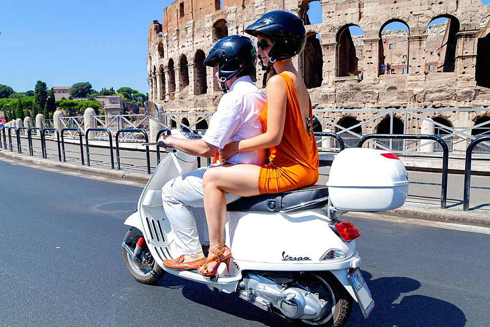 Couple riding a white vespa at the Roman Coliseum Rome Italy