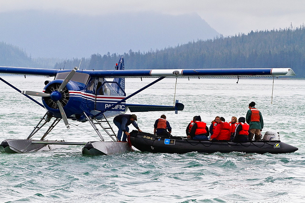 A view of a float plane loading Lindblad Expedition guests via Zodiac in Southeast Alaska, USA, Pacific Ocean