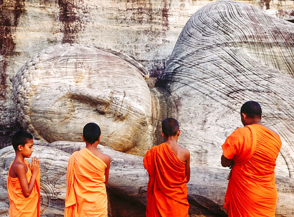 Monks praying at dawn in Gal Vihara temple, Polonnaruwa, Sri Lanka