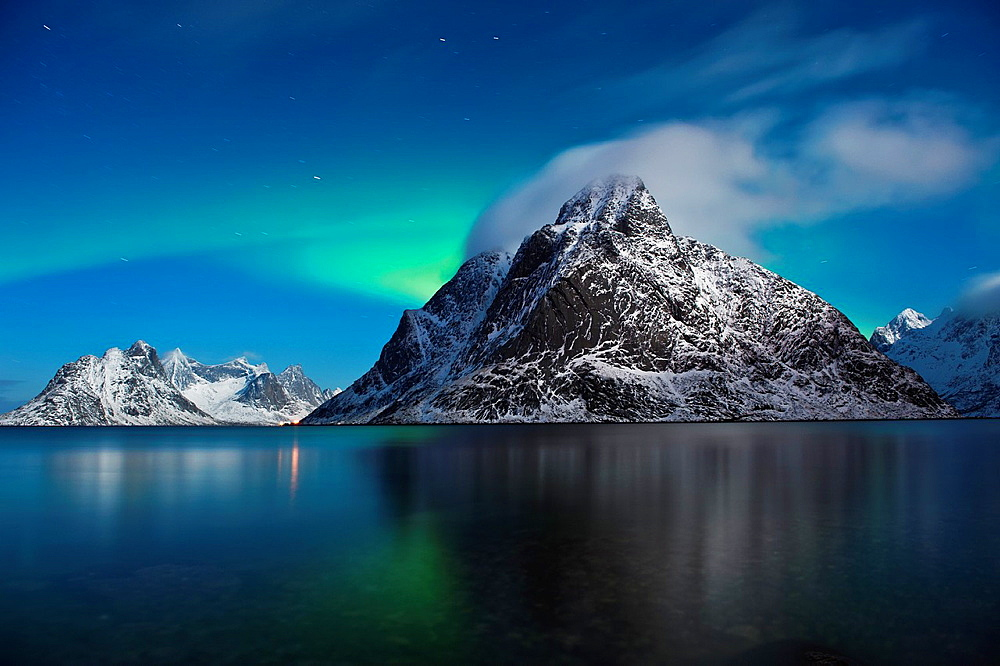 Northern Lights - Aurora Borealis in night sky behind Olstind mountain peak, Reine, Lofoten Islands, Norway