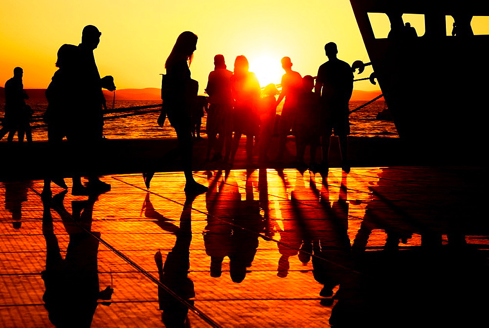People enjoying the sunset on a warm summer evening at the Sun Salutation on the ground in Zadar, Croatia  Designed by architect Nikola Basic, it harvests sun during the day and puts on a light show in the evening using the rhythm of the waves