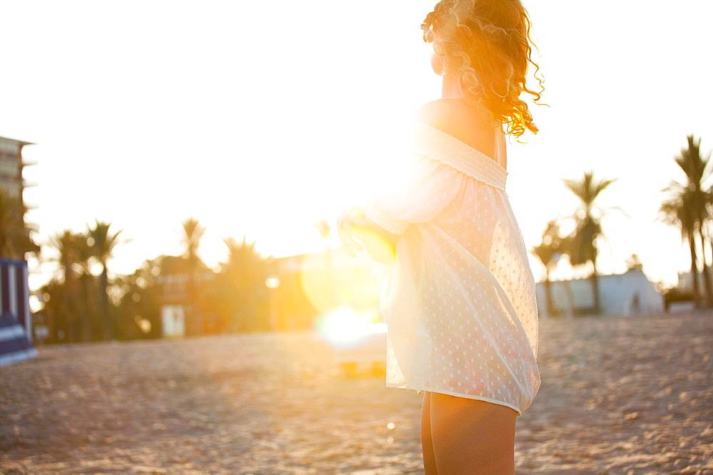Woman wearing cover up on beach. Sunset, San Juan beach, Alicante, Spain
