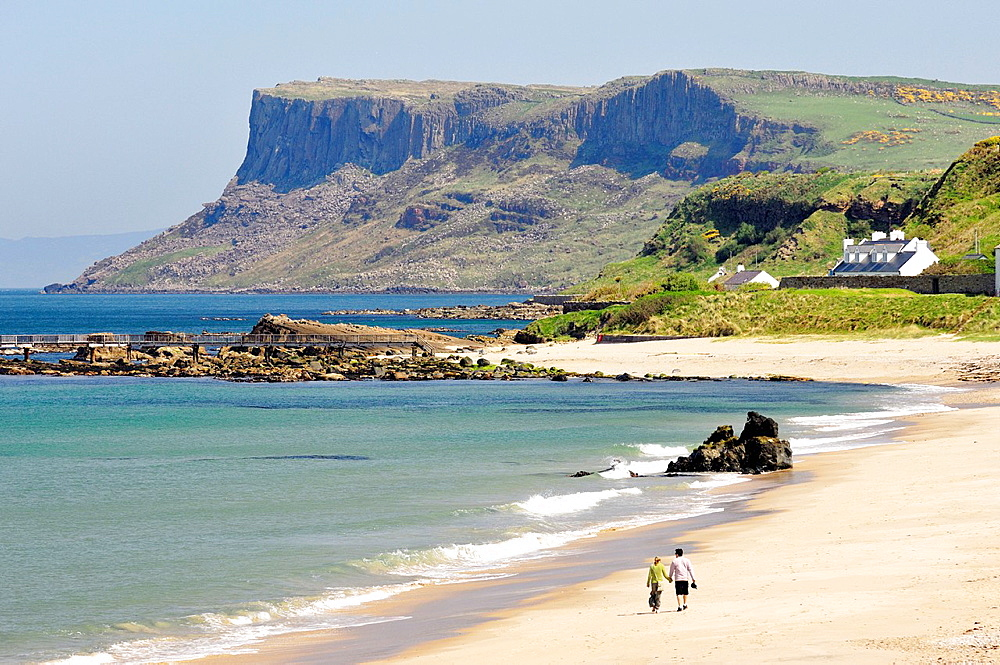Young couple walking on Ballycastle Beach, County Antrim, Northern Ireland  Looking toward the headland of Fair Head