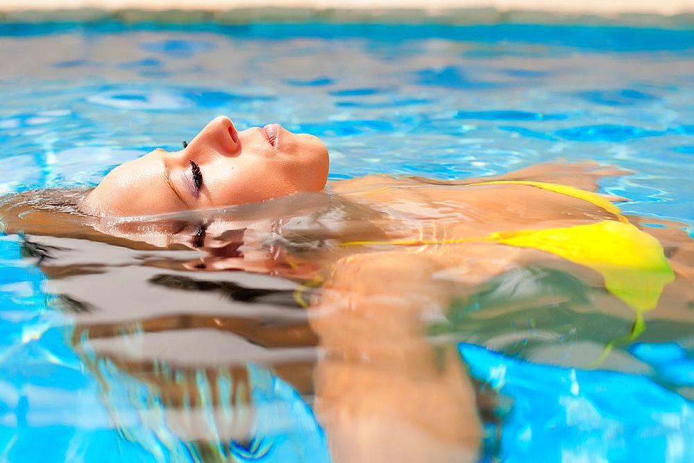 Beautiful woman in bikini enjoying a bath in a swimming pool