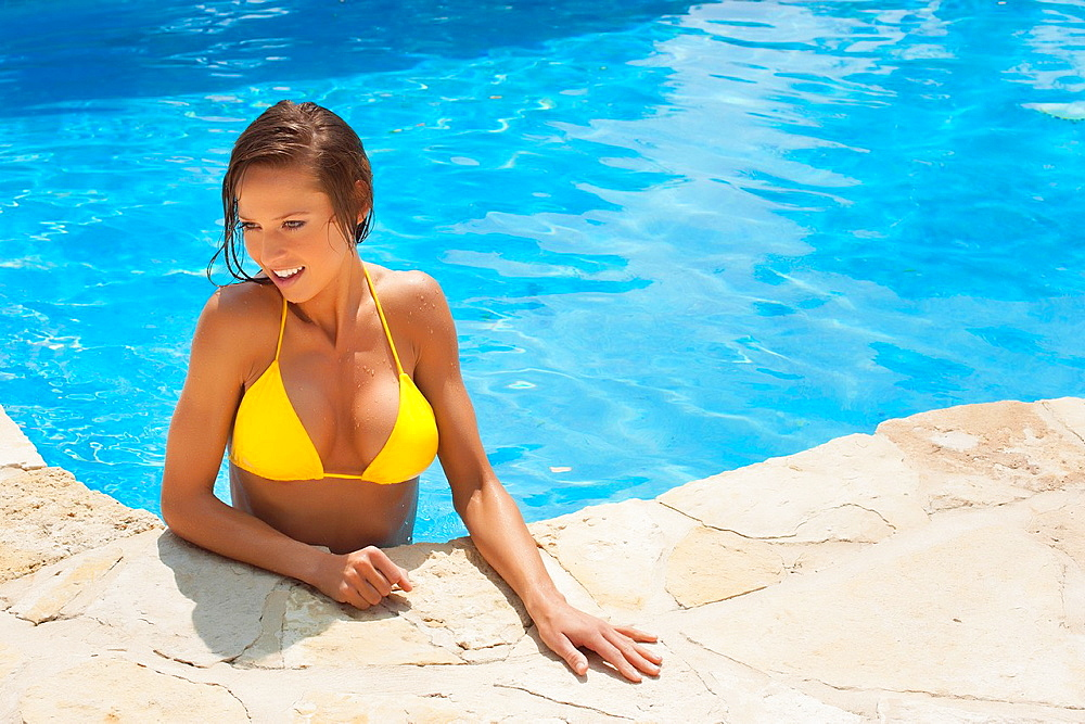 Beautiful young woman in bikini in a swimming pool - image with copyspace