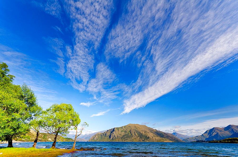 High altitude cirrus cloud streaks over lake Wanaka, South Island, New Zealand