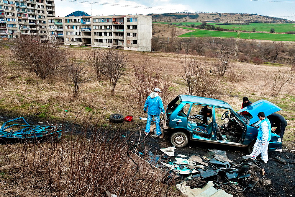 Gipsy men dismantle a used car to recycle metals in the Gipsy ghetto of Chanov on outskirts of Most, Czech Republic, 26 March 2008 - 817-392213