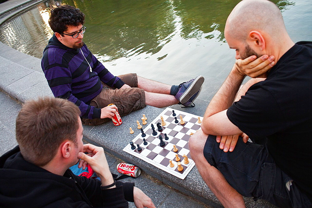 Friends playing chess,in front of Karlskirche St  Charles Borromeo church , Vienna, Austria