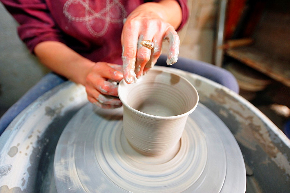 Female hands making pottery on spinning wheel