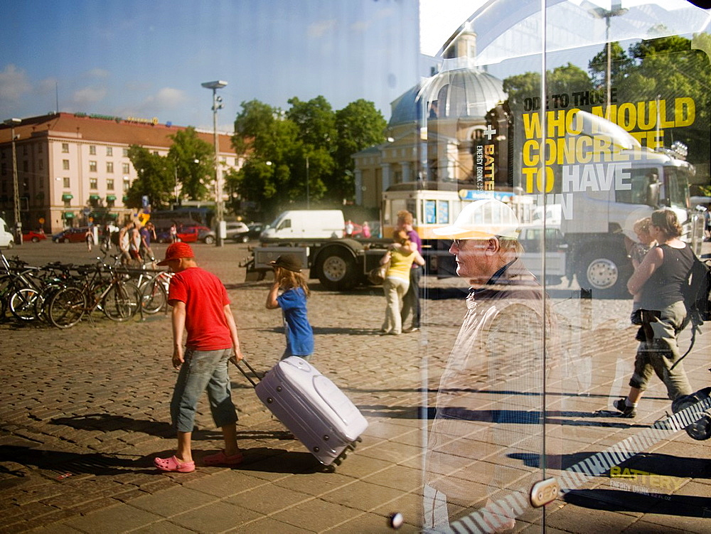Travellers reflected in glass at a bus stop in Turku, Finland