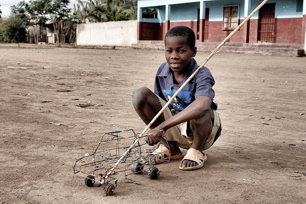 Child with a self-made toy, Chalucuane, Mozambique