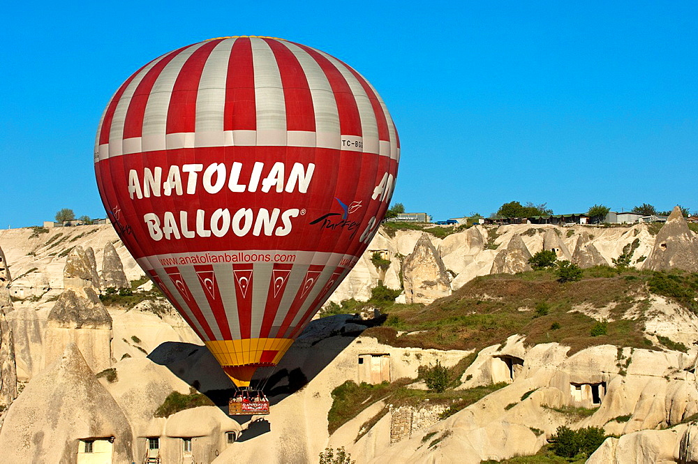 Hot air balloon of Anatolian Balloons landing in a tuffa rock site of Cappadocia, Goreme, Turkey