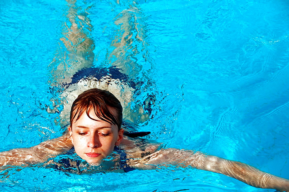 young woman swimmng in a swimming pool, close-up for face, front view