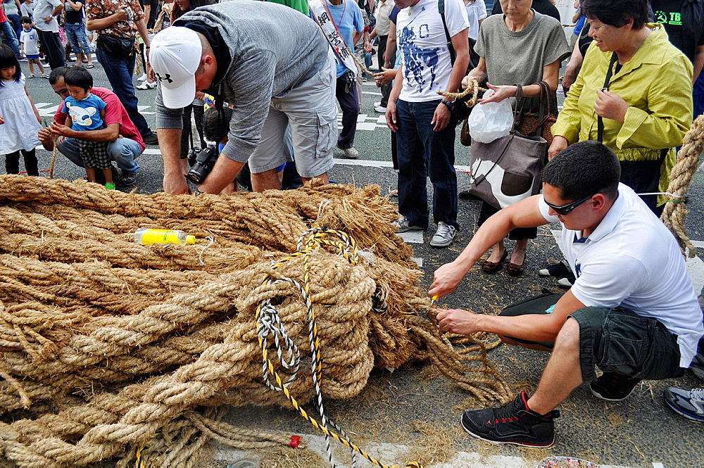 Naha, Okinawa, Japan, people cutting pieces of rope for good luck, during the Tug of war Festival, October