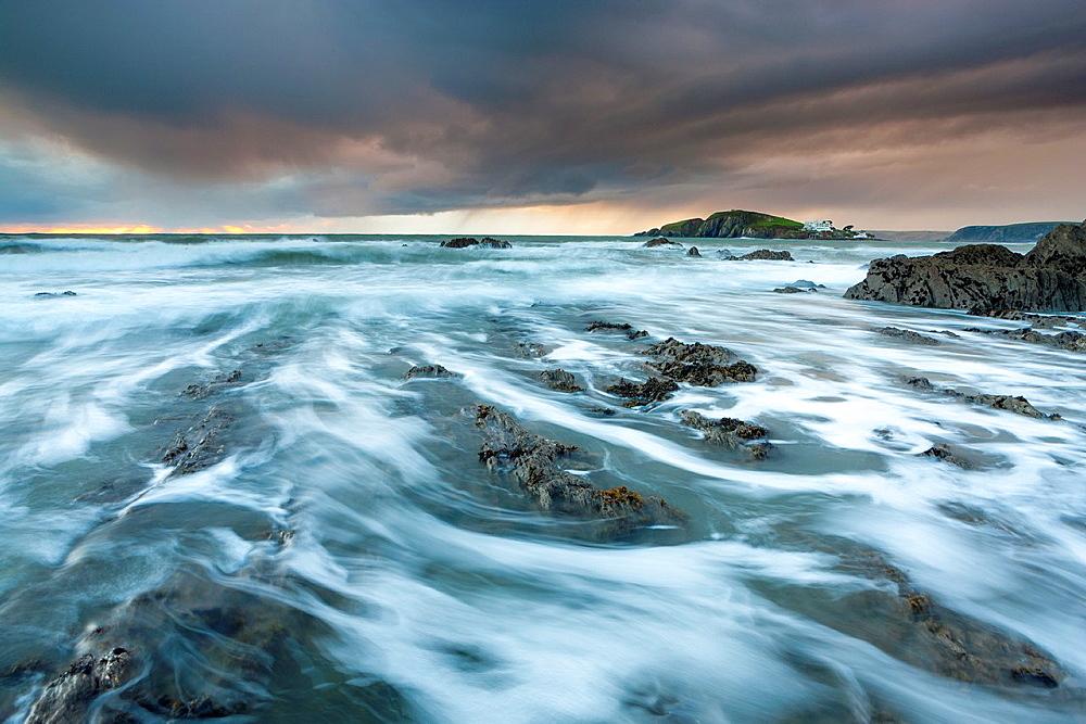 Rocky shores of Bantham at Dusk view towards Burgh Island, Devon, England, UK, Europe