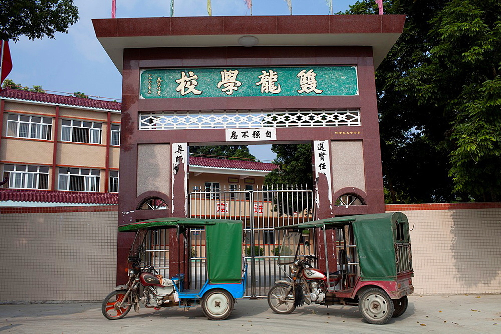 Old motor bike taxi parked at a newly built primary school in Jiexi, China.