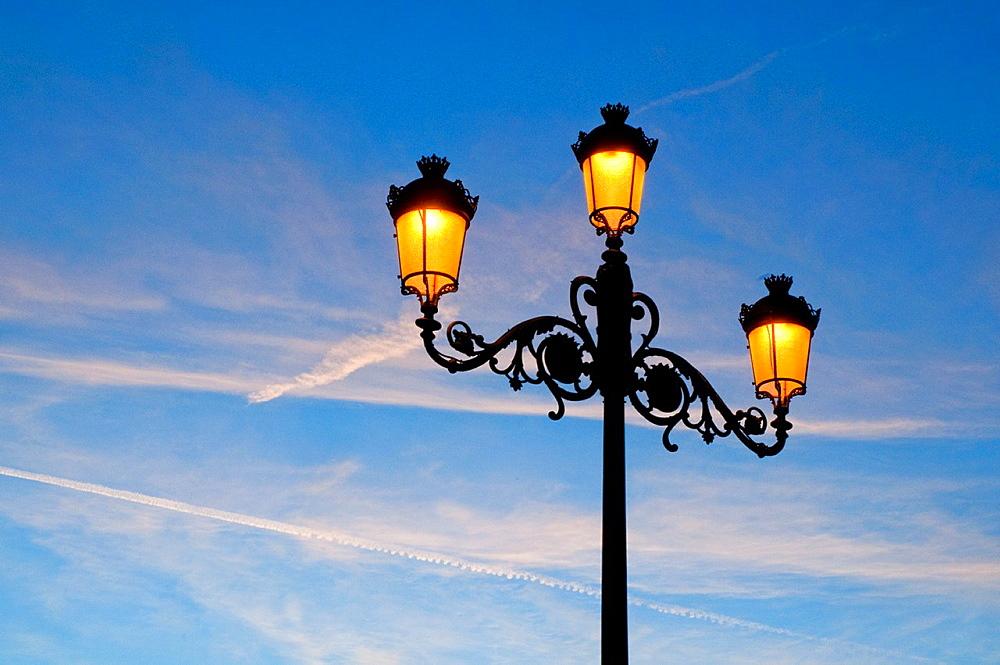 Lit up street light at dawn. The Retiro park, Madrid, Spain.