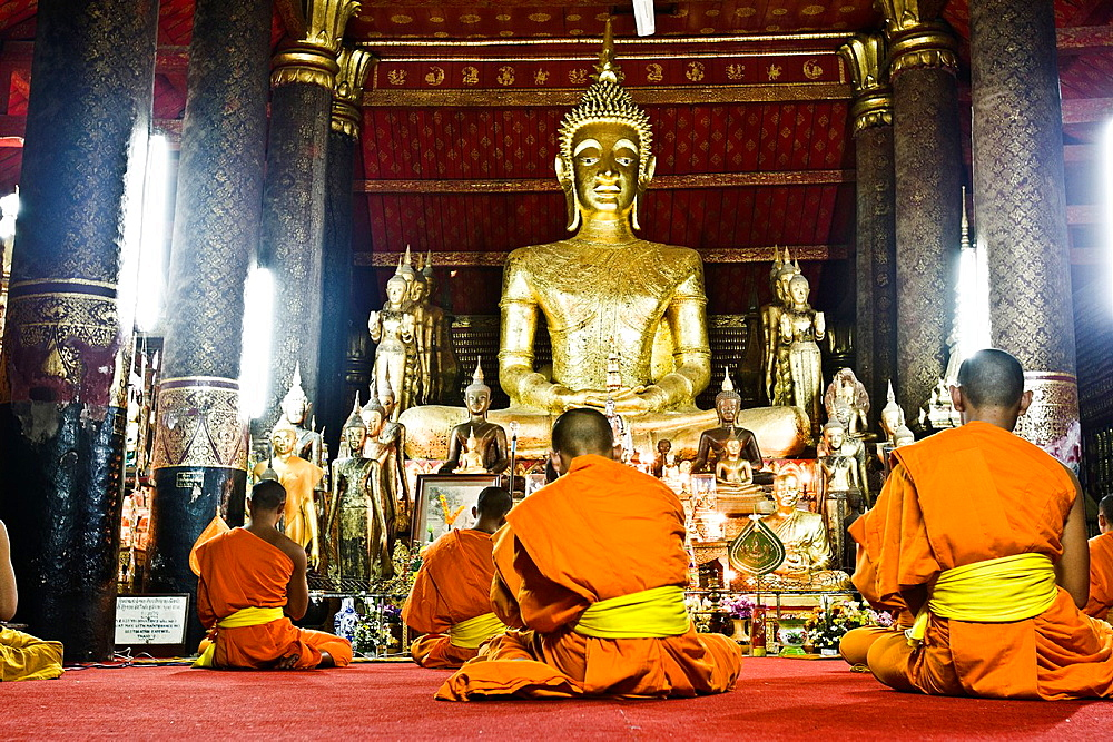 Monks praying in temple or wat Luang Prabang Laos