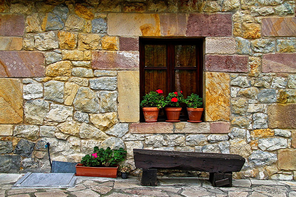 Wood bench outdoors the stone house, Santillana del Mar, Cantabria, Spain