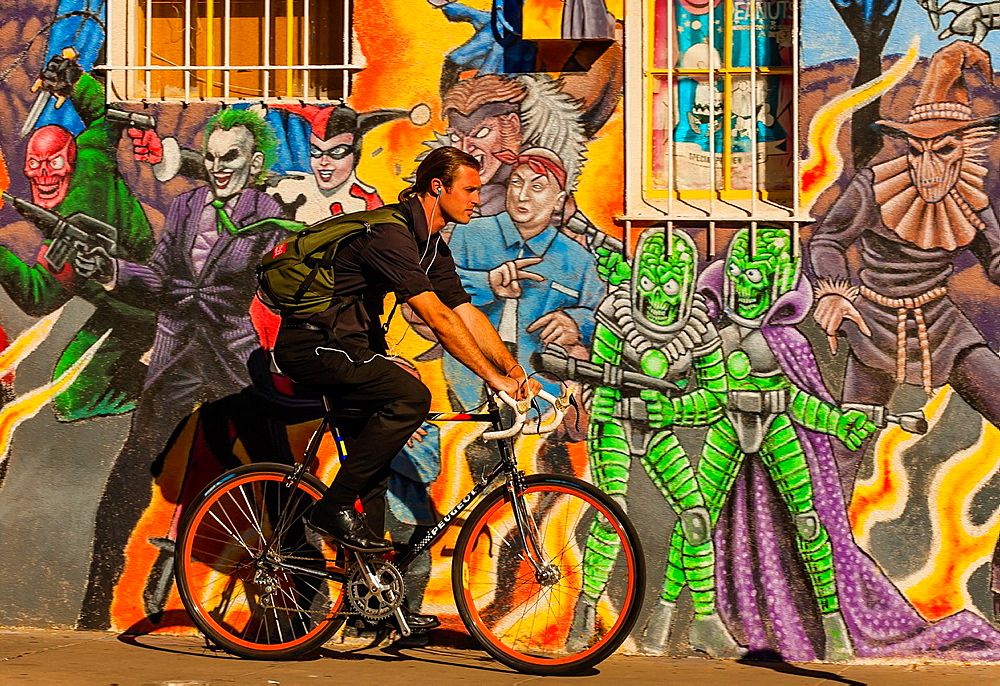 An urban bicyclist riding down the sidewalk with a mural of comic book super heroes on the side of ¥Masks Y Mas¥ store in background, Albuquerque, New Mexico USA - 817-417691