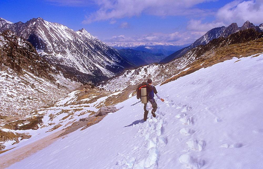 Hiker in `Portarro d¥Espot¥ Espot pass,going to `Estany de Sant Maurici¥Sant Maurici lake, Aiguestortes i Estany de Sant Maurici National Park, Pyrenees, Lleida province, Catalonia, Spain