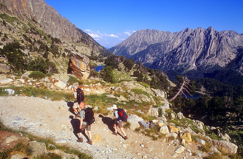Hikers climb to the Amitges refuge, in background at right Encantats mountains, Aiguestortes i Estany de Sant Maurici National Park,Pyrenees, Lleida province, Catalonia, Spain