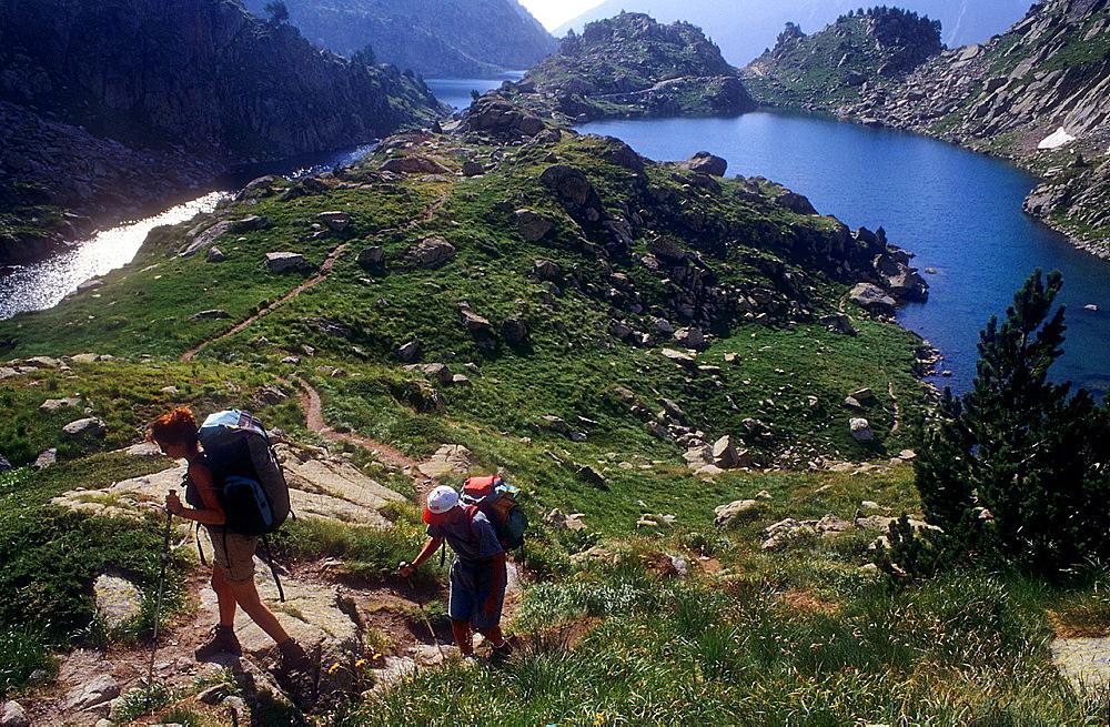 Trekking, in backgroun at right `Estany de Barbs¥Barbs lake, and at left estany de Munyidera¥Munyidera lake, Aiguestortes i Estany de Sant Maurici National Park,Pyrenees, Lleida province, Catalonia, Spain