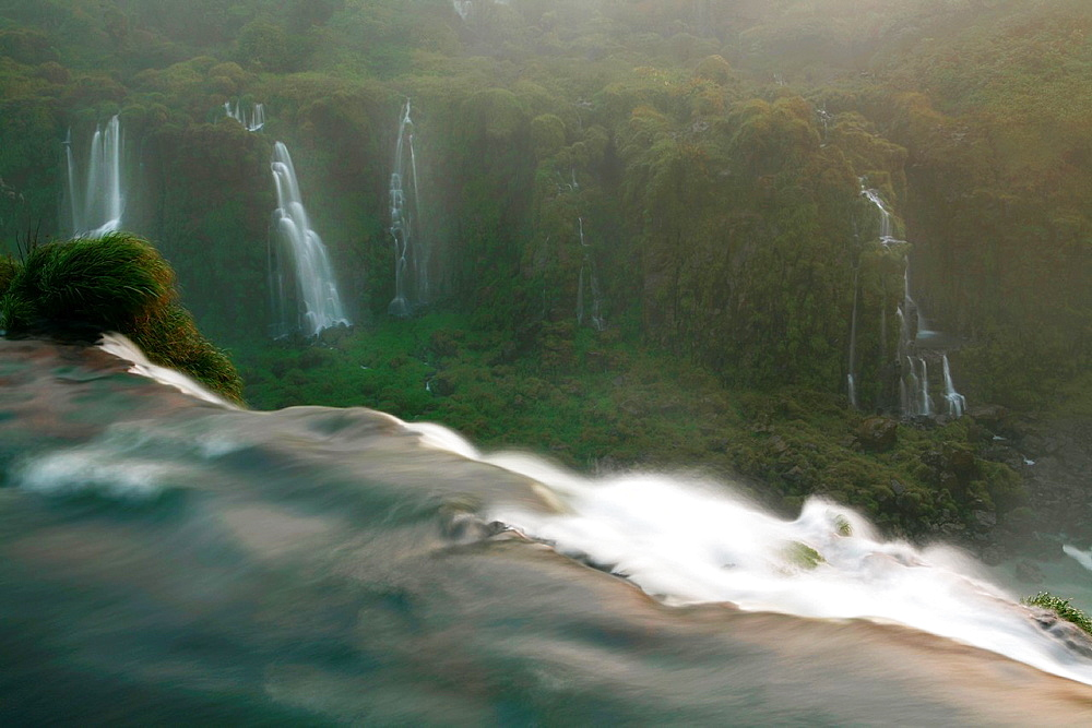 Looking over a Waterfall into the valley of more waterfalls at Iguacu Falls, Border of Brazil and Argentina