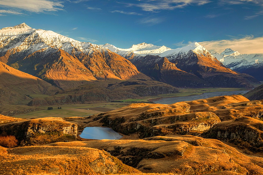 Dawn light across tussock grass hills above Matukituki River, Black Peak left and Mt Aspiring right, near Wanaka, Otago