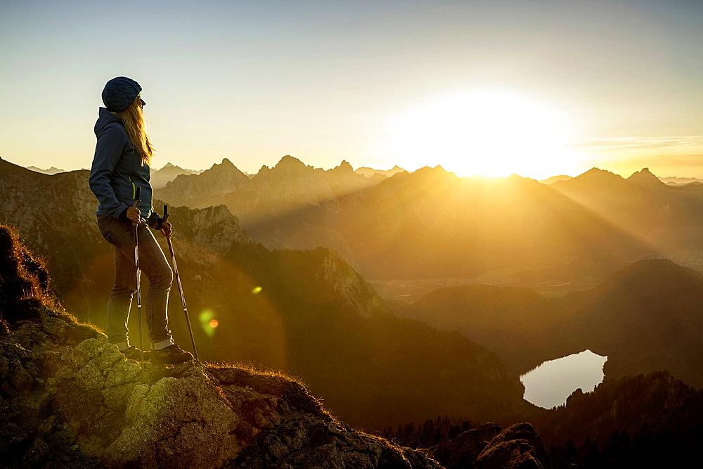 Hiker standing on rocky hilltop. Branderschrofen, Tegelber