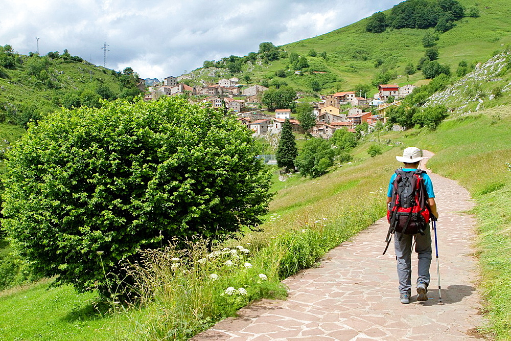 Hikers walking up to Tresviso, a small village in Picos de Europa National Park by historic Urdon path from La Hermida Gorges Penarrubia Cantabria, Spain