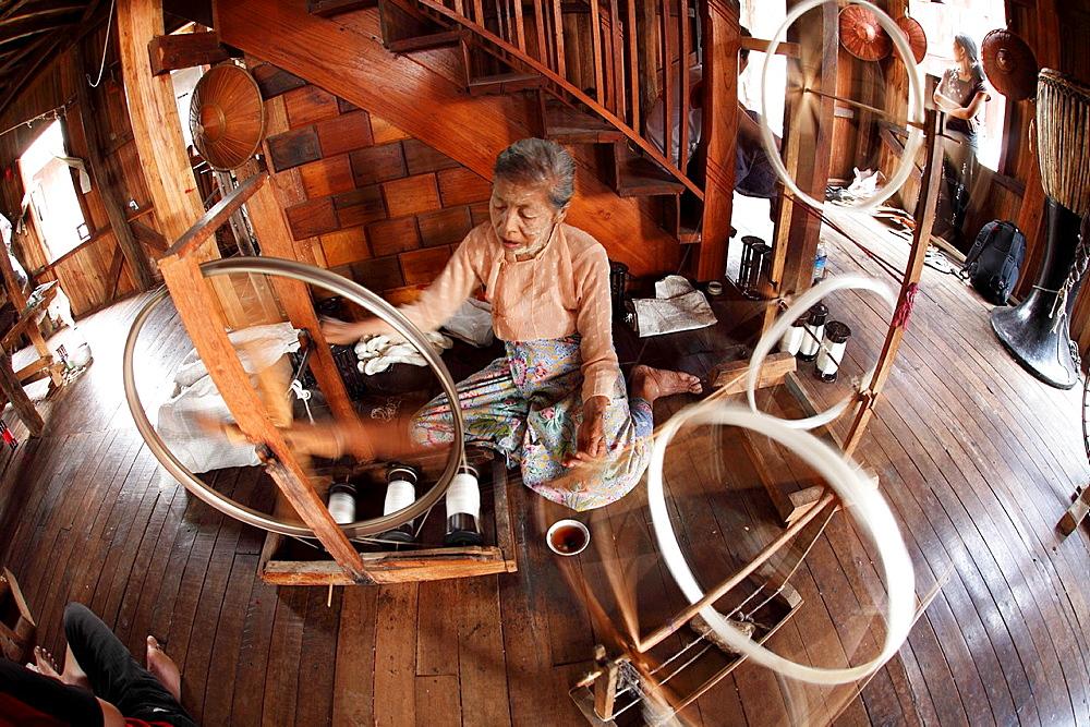 Intha woman spinning silk threads at a silk factory, Shan state, Myanmar, Burma
