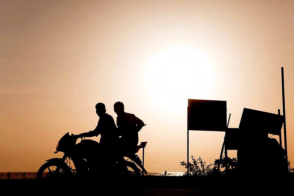 Backlight of a motorcycle with two people on the beaches of allepy