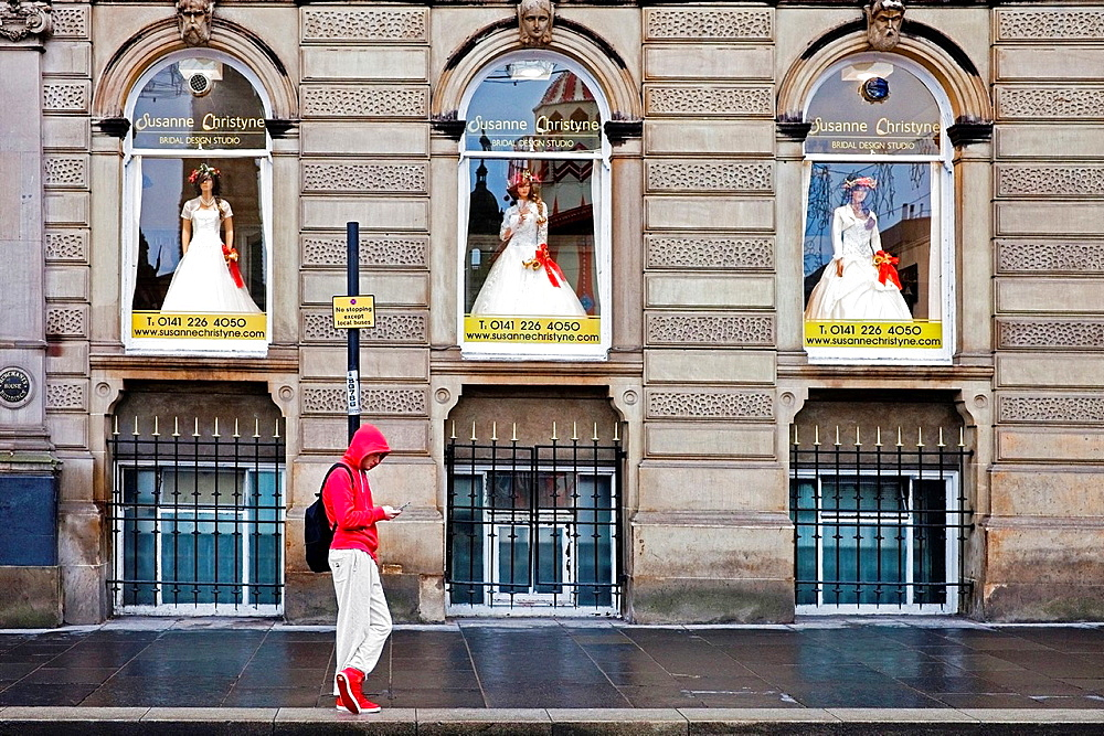 Young man looking at his phone outside a bridal shop, Queen Street, Glasgow, Scotland, Great Britain
