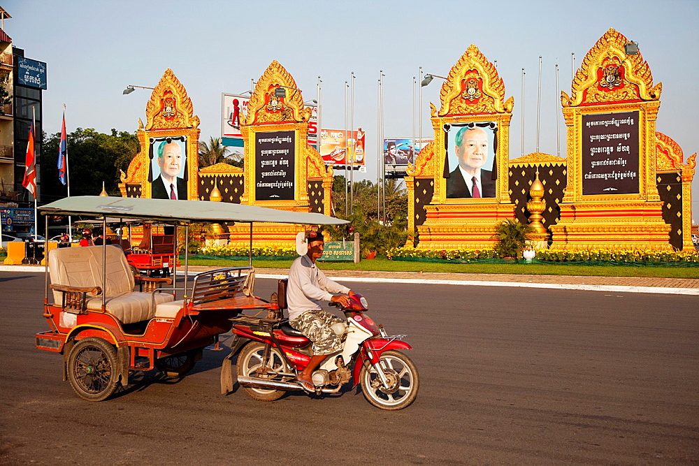 Tuk tuk driver driving in front of King Sihanouk portraits in Phnom Pen during the mourning of his death