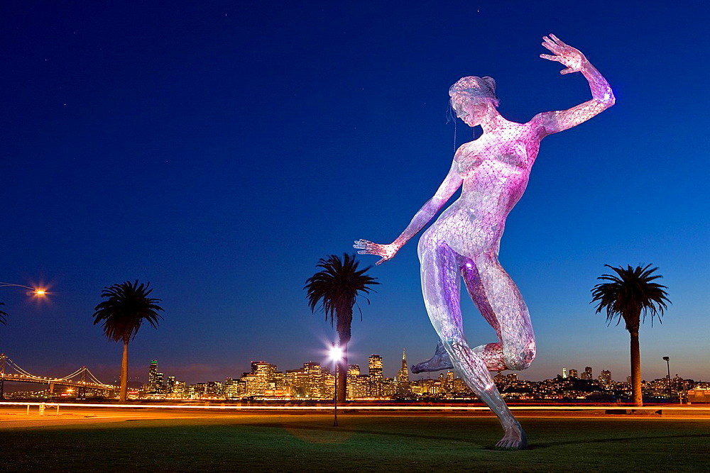 Bliss Dance', 40 foot high stainless steel mesh illuminated sculpture by Marco Cochrane, first exhibited at Burning Man, now on Treasure Island, San Franciso, California, USA, city skyline in distance, Bay Bridge on left, dusk - 817-423811