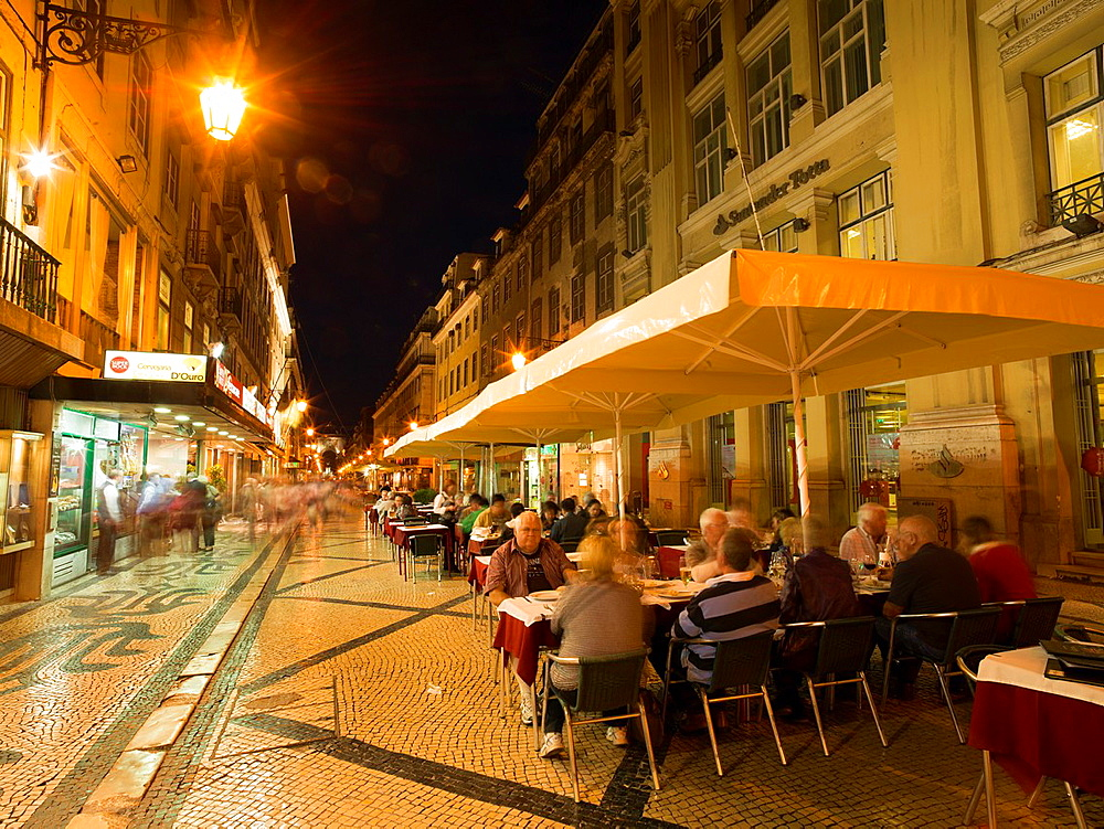 Portugal Lisbon. People in outdoor restaurant in Rua Augusta at evening.