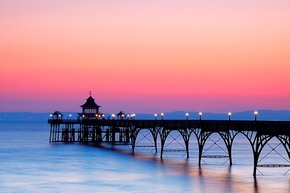 The Victorian pier in the Bristol Channel at the seaside town of Clevedon at dusk  North Somerset, England, United Kingdom