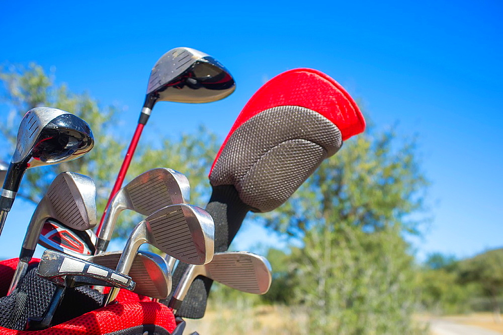 Set of golf clubs in a bag with blue sky in the background