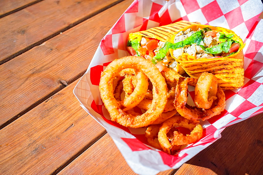Close up of fast food meal of chicken meat wrap and fried onion rings served in paper container