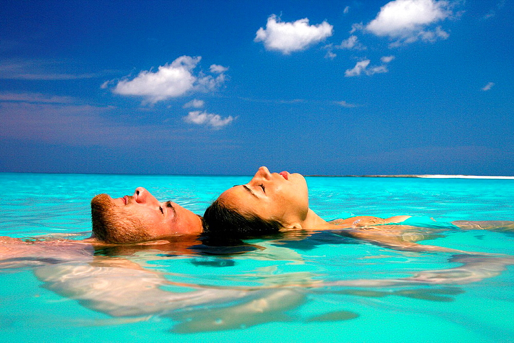 Couple floating in tropical ocean
