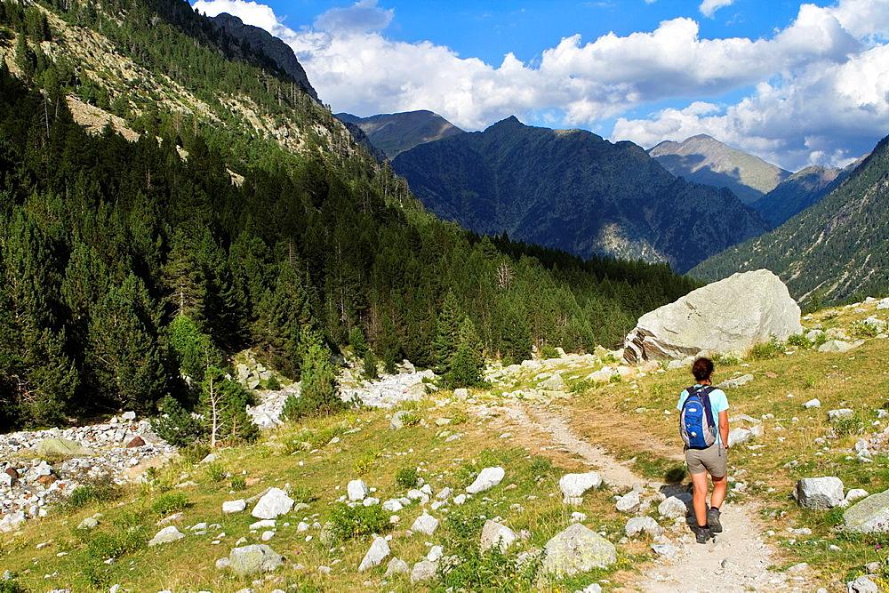Hiker walking along Barrosa valley, a typical glacier valley of aragonese Pyrenees Huesca Spain
