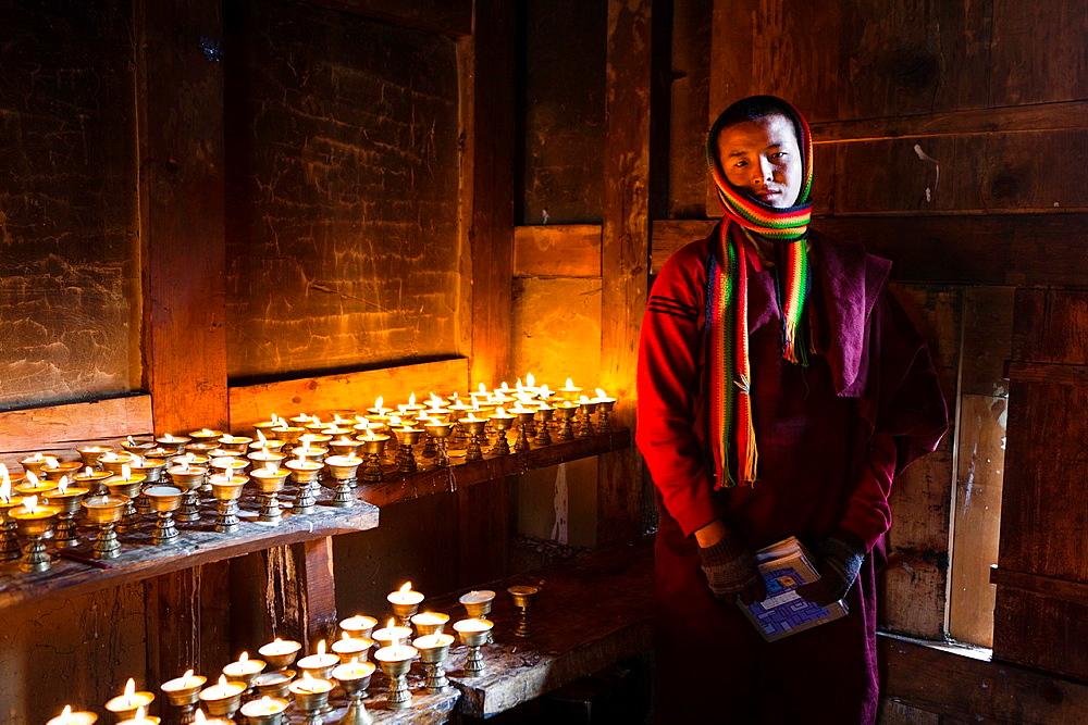 Monk in butter candle room, Gangtey Monastery, Gangtey, Bhutan, Asia.