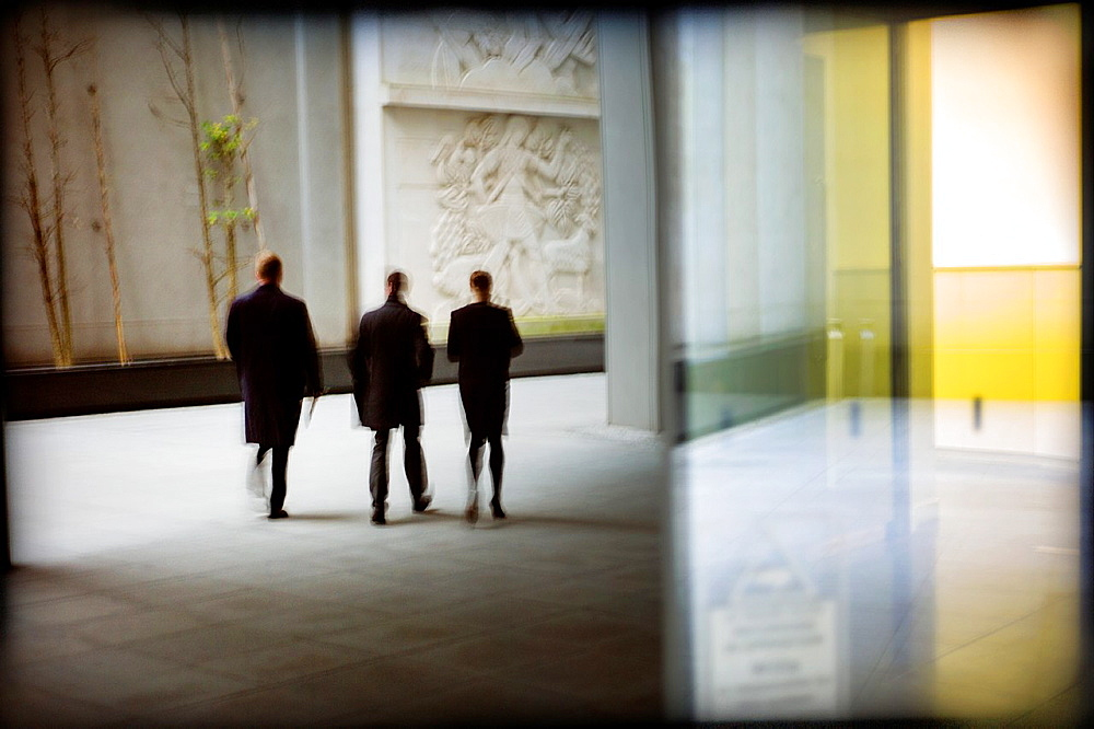 silhouette of three business men walking
