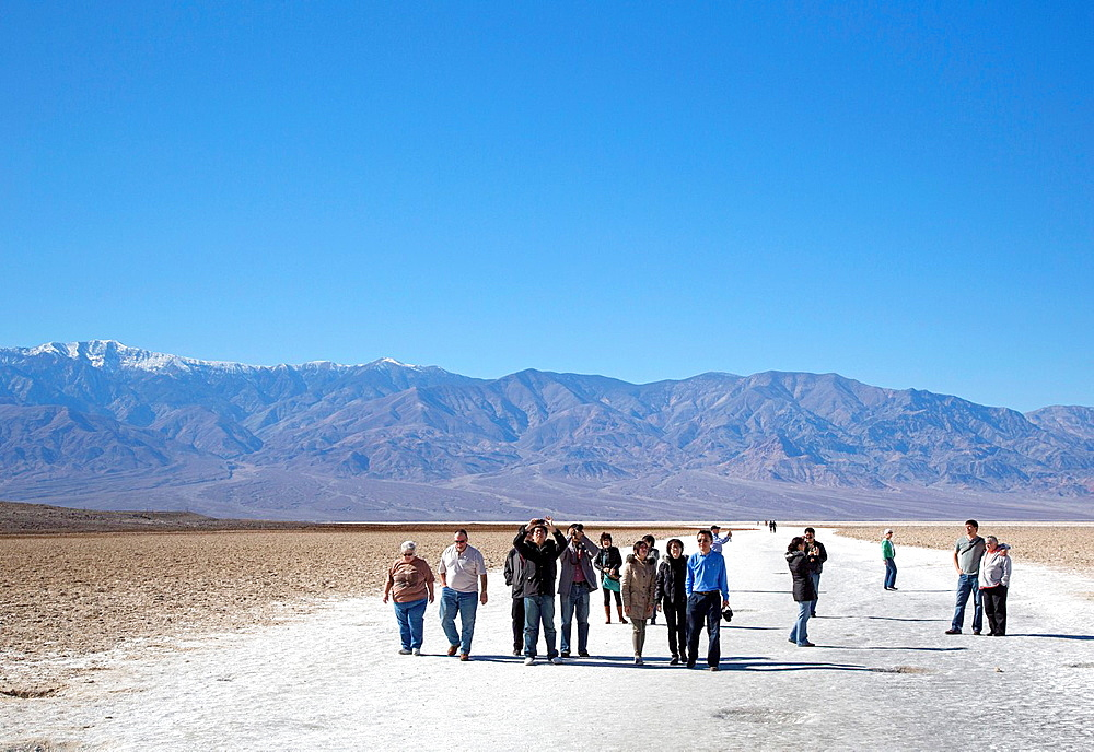 Death Valley National Park, California, Tourists on the salt flat in Badwater Basin At 282 feet 86 meters below sea level, this is the lowest spot in North America Snow-capped Telescrope Peak 11,049 feet is in the background
