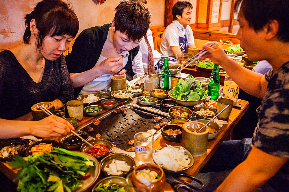 Friends eating Korean Barbeque, in Myeongdong restaurant, Myeongdong 8-gil street, Myeongdong shopping district, Seoul, South Korea