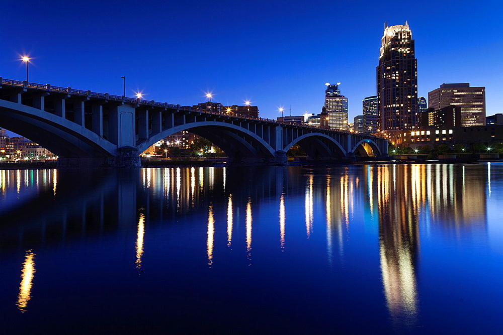 USA, Minnesota, Minneapolis, skyline with Third Avenue Bridge from Mississippi River, dusk